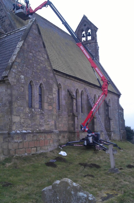 Sophie tracked spider cherrypicker working on church roof from slopped ground in churchyard.